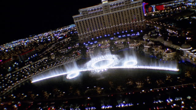 High angle wide shot Bellagio hotel and casino with fountains spraying at night / Las Vegas