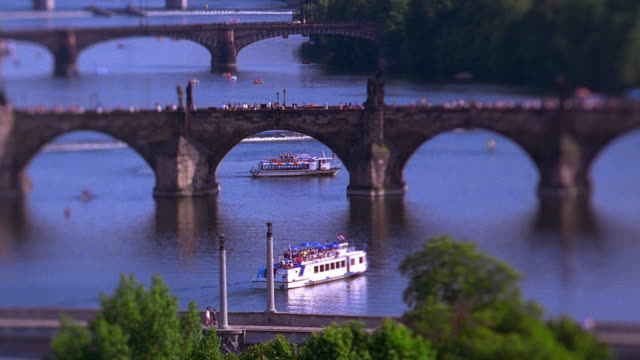high angle wide shot boats on vltava river with people on charles bridge and train passing in foreground / prague - vltava river stock videos & royalty-free footage