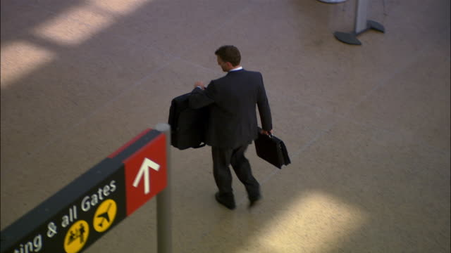 High angle wide shot businessman walking through airport with luggage/ Seattle