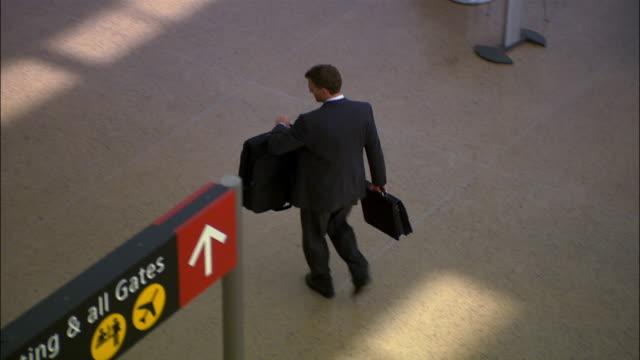 vídeos de stock, filmes e b-roll de high angle wide shot businessman walking through airport with luggage/ seattle - menos de 10 segundos