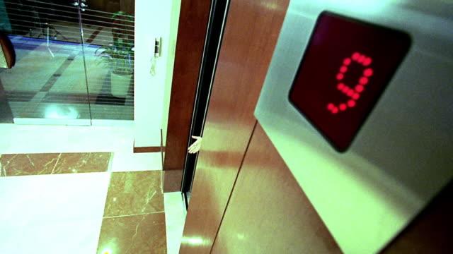 vídeos y material grabado en eventos de stock de high angle wide shot businesswoman, two businessmen + delivery man exiting elevator - encuadre de tres cuartos