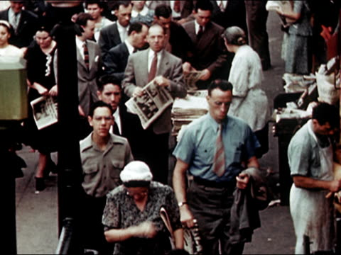 vidéos et rushes de 1945 high angle wide shot busy newspaper vendor on new york city street/ audio - vendeur ambulant