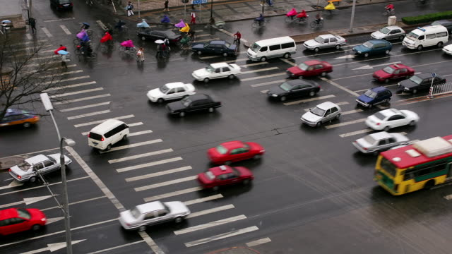High angle wide shot car, bicycle and pedestrian traffic at intersection on Xuanwumenwai Da Jie / Beijing, China