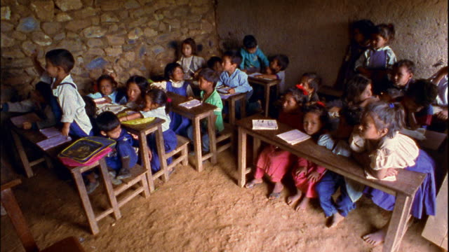 vídeos de stock e filmes b-roll de high angle wide shot children in small classroom within stone building / nepal - poverty