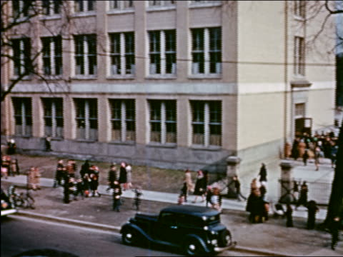 vidéos et rushes de 1941 high angle wide shot pan children walking in front of school building / chicago / industrial - prelinger archive