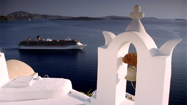 high angle wide shot church bell tower with cruise ship on water in background in the village of ia / santorini, greece - oia santorini stock videos & royalty-free footage
