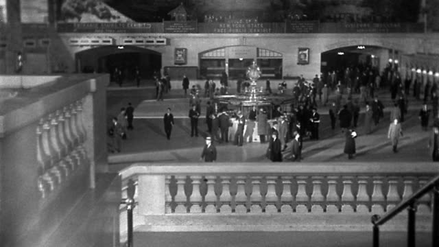 B/W high angle wide shot commuters walking in Grand Central Station with clock / New York City