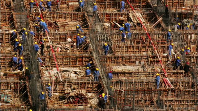 high angle wide shot construction workers building on the dawn male hospital site / beijing, china - baugewerbe stock-videos und b-roll-filmmaterial