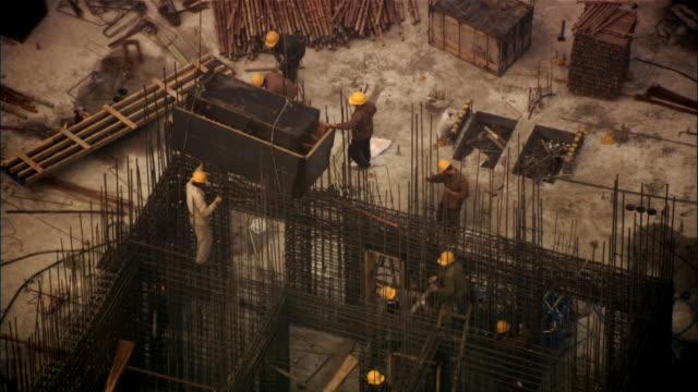 vídeos y material grabado en eventos de stock de high angle wide shot contruction workers and frame of metal rods/ beijing, china - noreste de china