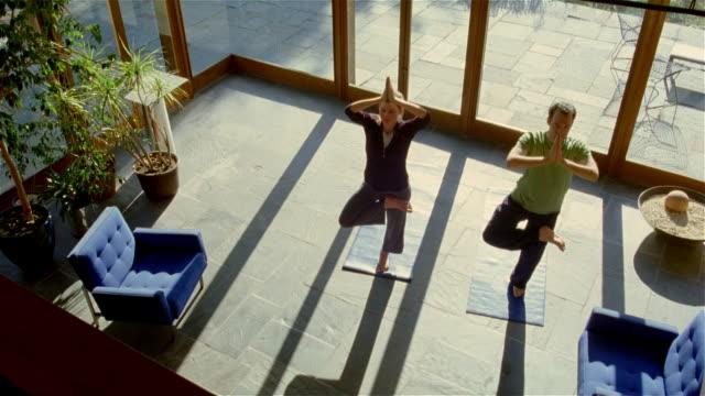 vídeos y material grabado en eventos de stock de high angle wide shot couple doing yoga in living room/ solebury, pennsylvania - vriksha asana