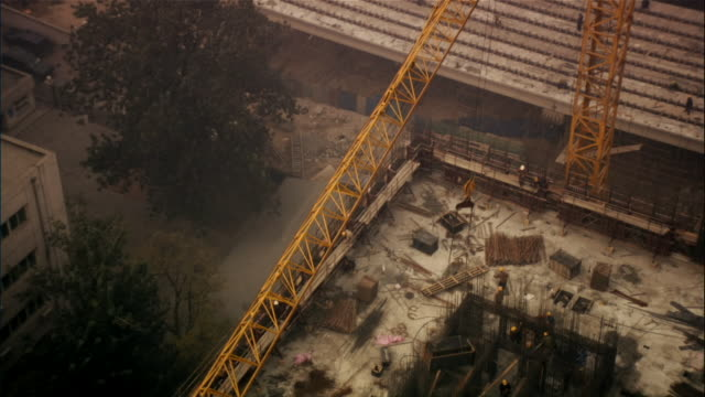 vídeos y material grabado en eventos de stock de high angle wide shot crane lifting large item over workers at construction site/ beijing, china - noreste de china