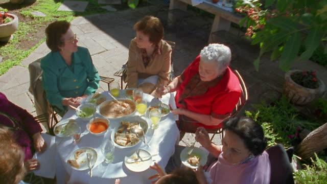 high angle wide shot crane shot group of senior women sharing meal on patio - looking down stock videos and b-roll footage