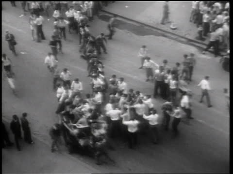 B/W 1931 high angle wide shot crowd of male Columbia University students fighting on street / NYC / newsreel