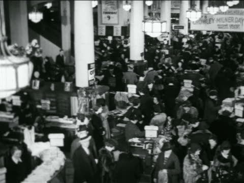 B/W 1938 high angle wide shot crowd of shoppers in department store / industrial