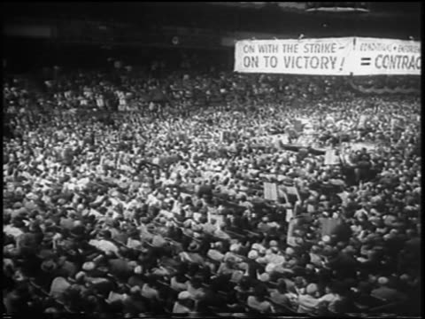 b/w 1958 high angle wide shot pan crowd of striking garment workers in madison square garden rally nyc / newsreel - 1958 stock videos & royalty-free footage