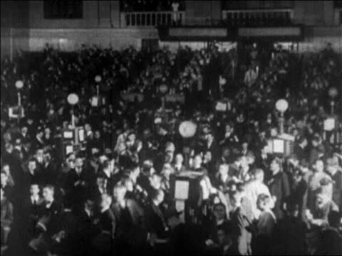 b/w 1929 high angle wide shot crowd on floor of new york stock exchange / papers flying in foreground / newsreel - 1929 stock videos & royalty-free footage
