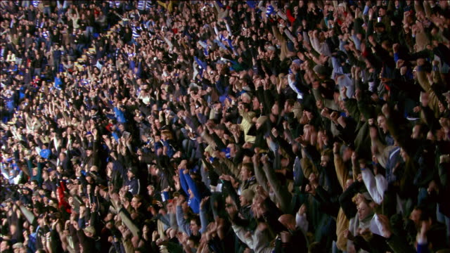high angle wide shot crowd watching soccer match at madejski stadium / standing up and cheering / reading, england - eccitazione video stock e b–roll