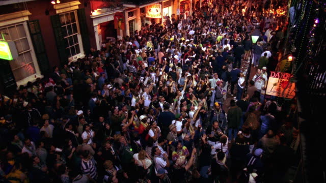 high angle wide shot crowds of people celebrating mardi gras on bourbon street at night / new orleans, louisiana - new orleans stock videos and b-roll footage