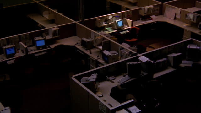 high angle wide shot dark empty office with cubicles + computers / desk lamp on at one desk - オフィスパーテーション点の映像素材/bロール