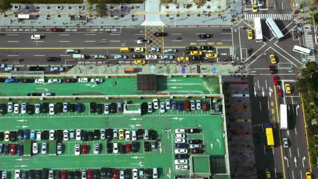 high angle wide shot daytime traffic in and around rooftop parking lot below taipei 101 building / taipei, taiwan - taiwan stock videos & royalty-free footage