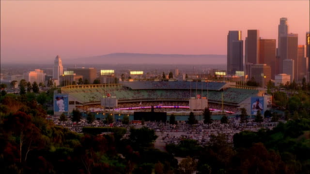 High angle wide shot Dodger Stadium with downtown skyline in background / dusk / Los Angeles, California