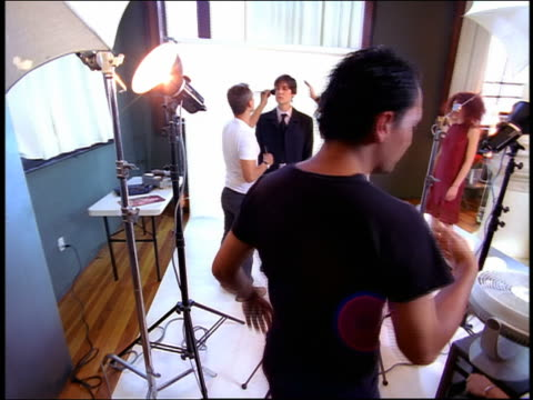 high angle wide shot dolly shot makeup artist and hairdresser working on male model in studio with photographer in foreground - photo shoot stock videos & royalty-free footage