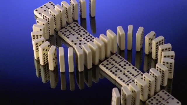 high angle wide shot dominoes shaped in dollar sign falling - dominoes stock videos & royalty-free footage