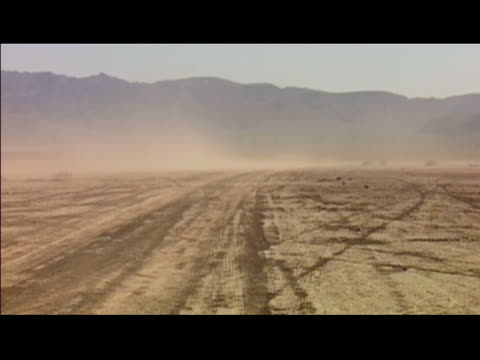 2001 high angle wide shot dust storm in desert with mountains in background/ nevada - tire track stock videos & royalty-free footage