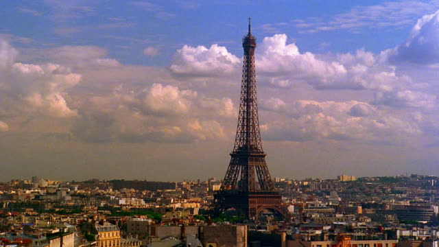 High angle wide shot Eiffel Tower and Paris skyline with clouds rolling in background / France