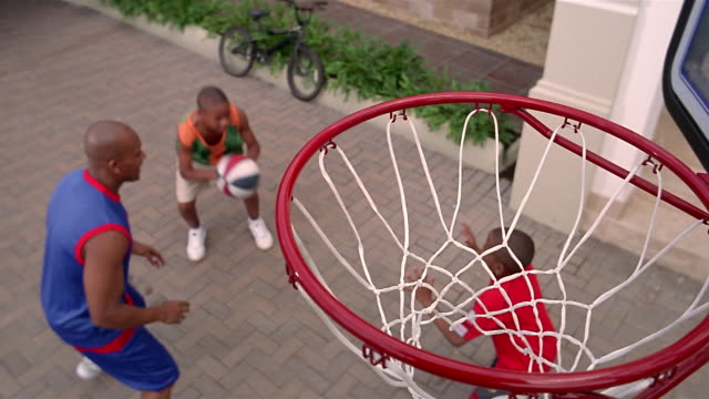 vídeos de stock, filmes e b-roll de high angle wide shot father and two sons playing basketball in driveway / father lifting son up to hoop - entrada para carros
