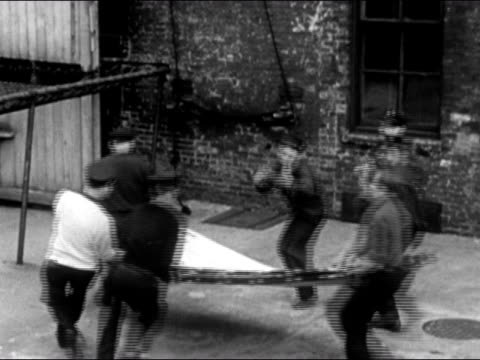 1947 high angle wide shot firemen run up to side of building and open jumping sheet/ dearborn, michigan - dearborn michigan stock videos and b-roll footage