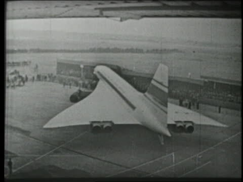 b/w 1969 high angle wide shot first concorde plane being towed out of airplane hangar in france - british aerospace concorde stock videos & royalty-free footage