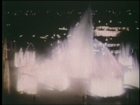 1964 high angle wide shot fountains shooting fireworks at night / ny world's fair - esposizione universale di new york video stock e b–roll