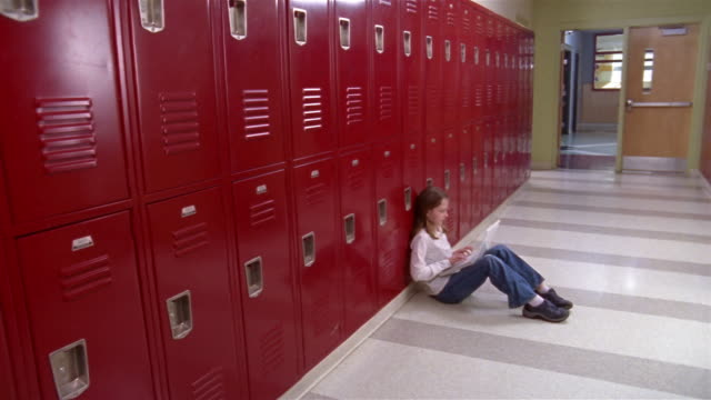 high angle wide shot girl sitting, typing on laptop against school lockers/ pan close up lockers/ pan wide shot girl typing/ goram, maine - spind stock-videos und b-roll-filmmaterial