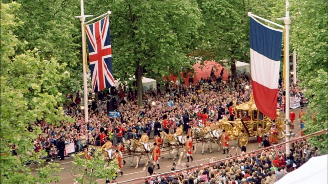 high angle wide shot gold horsedrawn carriage passing flags of uk and france in british ceremonial procession - royalty stock videos & royalty-free footage