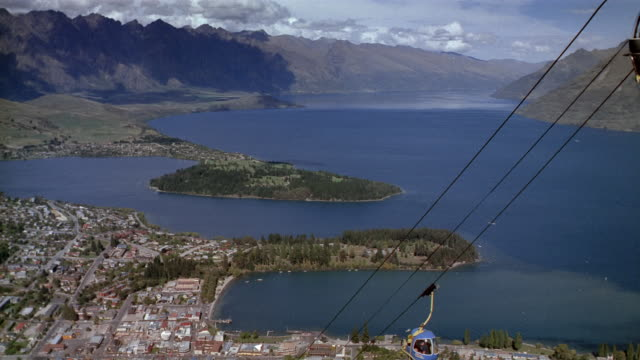 High angle wide shot gondola lift with view of Lake Wakatipu and Remarkables / Queenstown, South Island, New Zealand