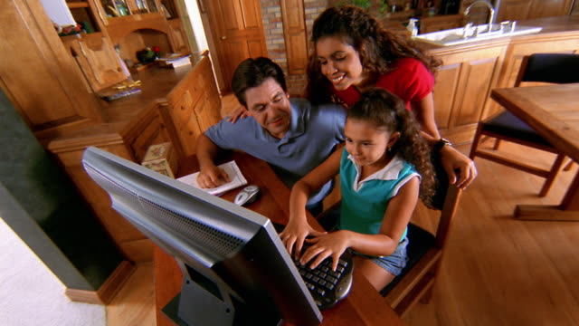 high angle wide shot hispanic family at computer in kitchen - daughter video stock e b–roll