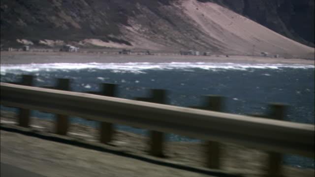 vídeos de stock e filmes b-roll de high angle wide shot horizon over ocean and waves crashing on rocky coast/ malibu, california - pacífico norte
