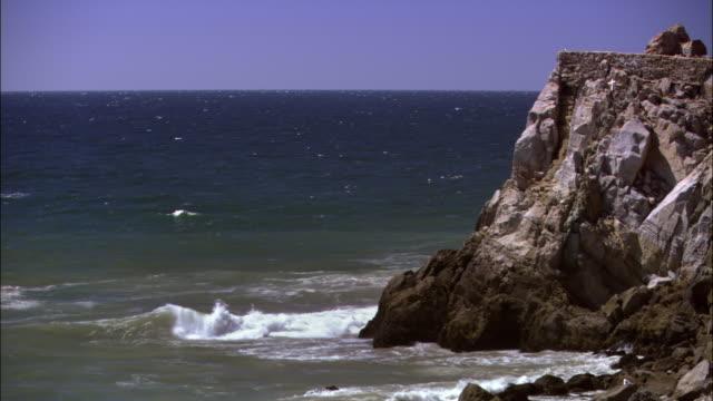vídeos de stock e filmes b-roll de high angle wide shot horizon over ocean with white cross on rocky cliff/ malibu, california - pacífico norte