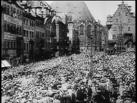 vídeos de stock, filmes e b-roll de high angle wide shot huge crowd in plaza at nazi rally at nuremberg / germany / newsreel - 1920 1929