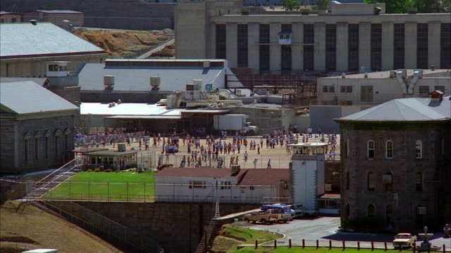 high angle wide shot inmates walking around prison yard / playing sports and exercising - 囚人点の映像素材/bロール