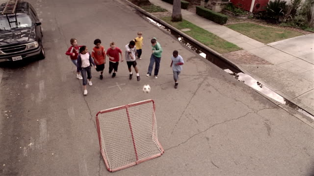 High angle wide shot kids playing soccer in street / boy kicking ball into goal