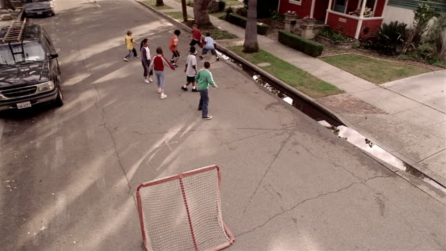 High angle wide shot kids playing soccer in street / boy kicking ball and missing goal