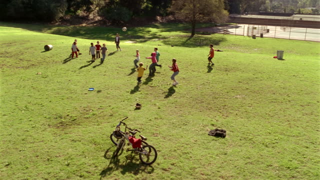 vidéos et rushes de high angle wide shot kids playing soccer - square