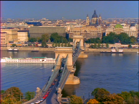 high angle wide shot large boat passing under chain bridge on danube river / budapest, hungary - river danube stock videos & royalty-free footage