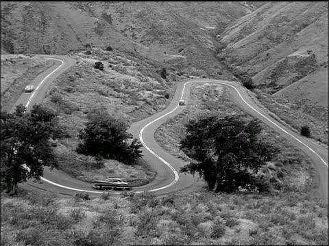 b/w 1957 high angle wide shot light traffic on winding desert mountain road - 1957 stock-videos und b-roll-filmmaterial