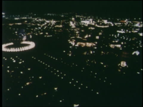 1964 high angle wide shot pan of lit ny world's fair at night - esposizione universale di new york video stock e b–roll