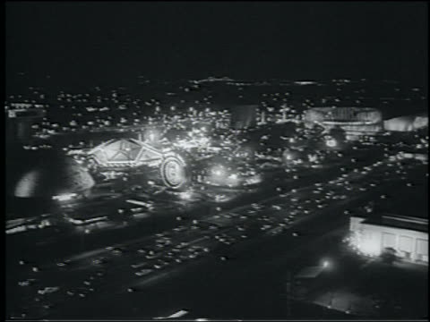b/w 1964 high angle wide shot lit ny world's fair traffic on highway at night - esposizione universale di new york video stock e b–roll