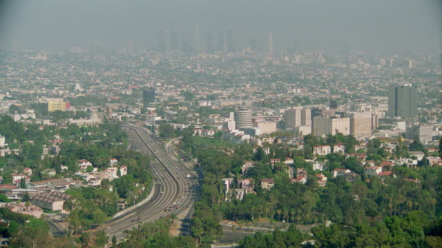 high angle wide shot long shot los angeles skyline with traffic on highway in foreground / heavy smog obscuring skyline - wide shot stock videos & royalty-free footage