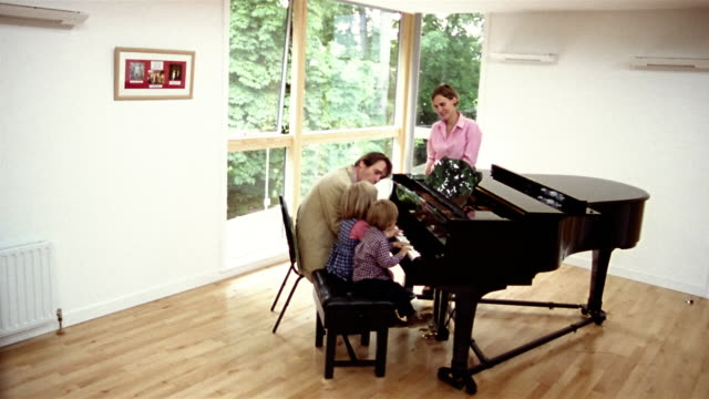 High angle wide shot man giving son and daughter piano lesson as wife looks on / pan to picture on wall